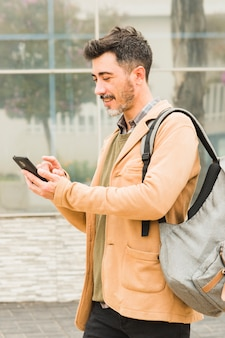 Smiling modern man with his backpack using mobile phone