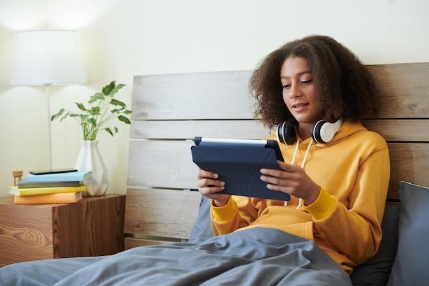Улыбающаяся современная девушка-подросток смешанной расы с наушниками на шее сидит под пуховым одеялом в постели и читает статью на планшете