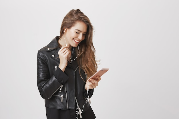 Улыбается современная женщина в кожаной куртке, пользуется мобильным телефоном и слушает музыку в наушниках