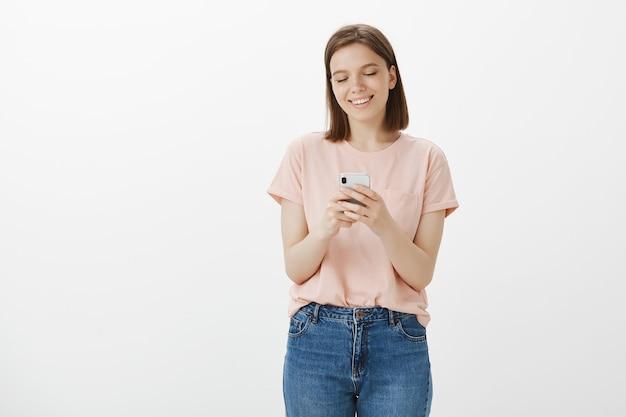 Sorridente donna moderna utilizzando il telefono cellulare, mandare sms sui social network