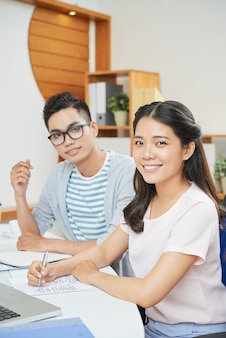 Smiling modern woman with man in office