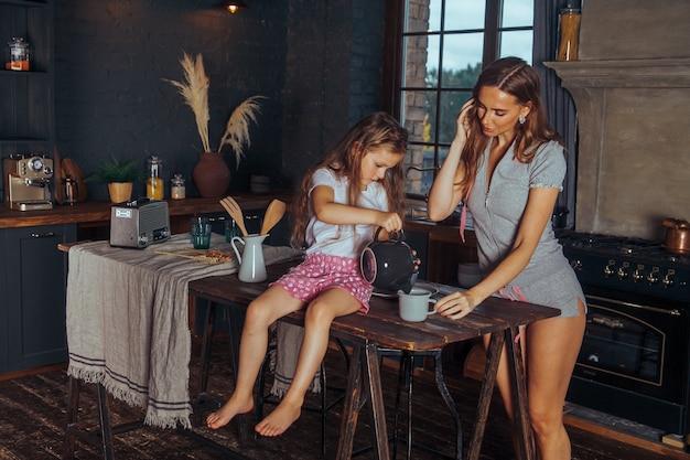 笑顔のママと子娘の女の子が自宅の暗いキッチンで料理をして楽しんでいます。