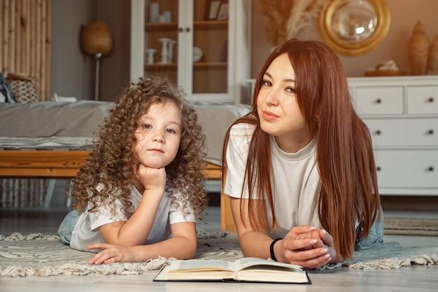 Улыбающаяся мама и дочь дошкольника с книгой смотрят в камеру, лежа на полу дома, солнечный свет
