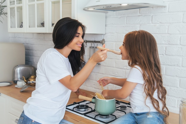 Smiling mom and daughter cooking in the scandinavian-style kitchen on white