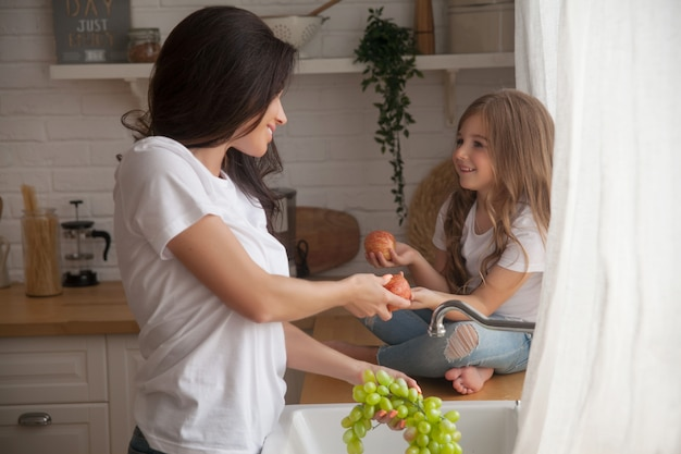 Smiling mom and daughter washing fruits in a scandinavian-style kitchen.