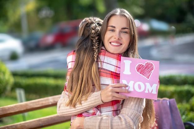 Улыбающаяся мама обнимает свою дочь и держит открытку