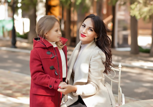 Smiling mom helps little cute daughter fasten her red coat.