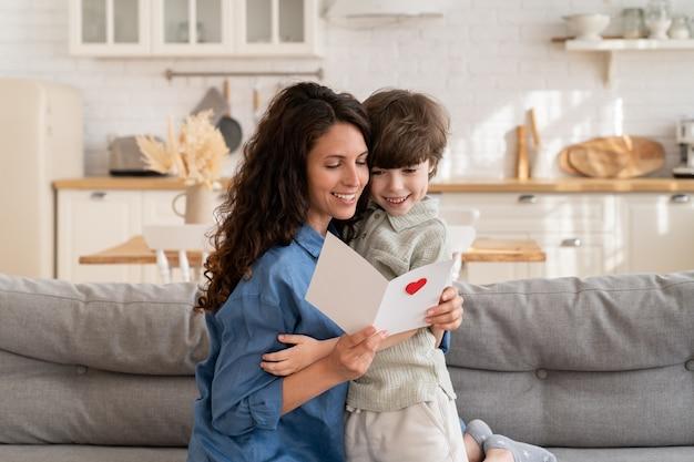 幸せな母の日や誕生日に笑顔のお母さんがはがきを持って未就学児の息子からの挨拶の願いを読む