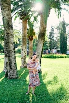 笑顔のお母さんは、ヤシの木の下で彼女の腕に小さな女の子を保持します