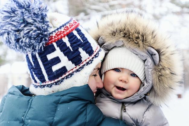 Улыбающаяся мама в зимней одежде обнимает ребенка зимой в парке, концепция безусловной любви