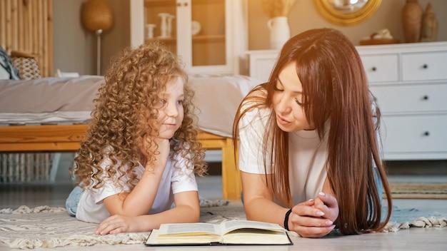 Улыбающаяся мама читает сказку из книги, лежа на полу возле задумчивой дочери-дошкольника с длинными распущенными вьющимися волосами дома, солнечный свет