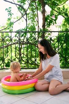 웃는 엄마는 풍선 수영장에 있는 어린 소녀 옆 바닥에 앉아 있다