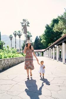 笑顔のお母さんは公園の舗装された小道に沿って小さな女の子と一緒に歩きます