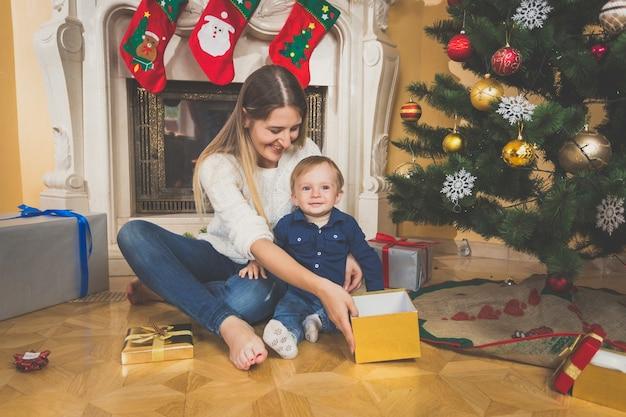 クリスマスプレゼントを見て床に笑顔の母と赤ちゃん