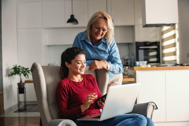 Улыбающиеся мать и дочь дома. дочь сидит в кресле и использует технологии, в то время как мать наклоняется и смотрит на нее.