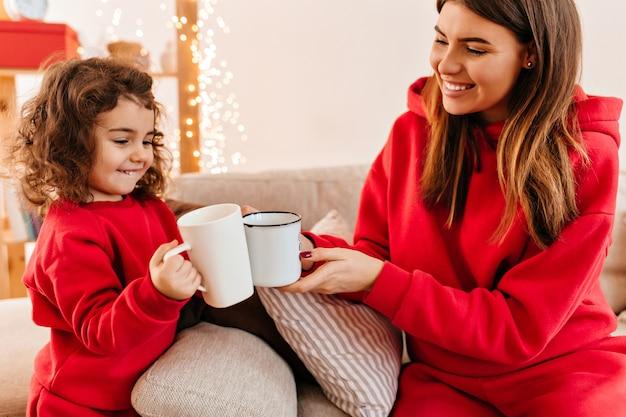 ティーカップを持って笑顔の母と娘。週末にソファでポーズをとって笑っている家族のスタジオショット。