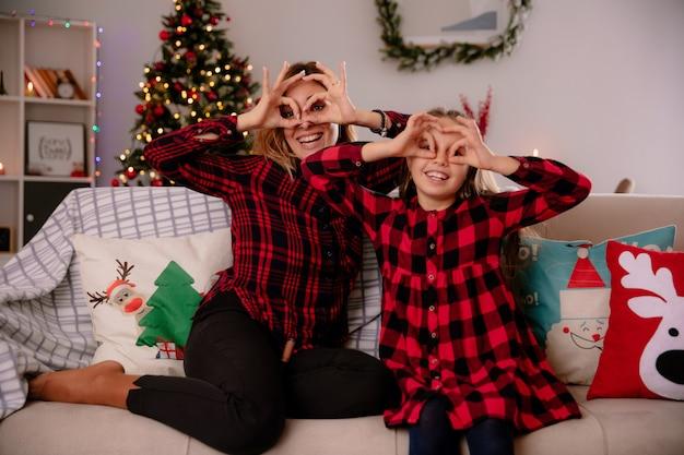 웃는 엄마와 딸 소파에 앉아 집에서 크리스마스 시간을 즐기는 손가락을 통해보고
