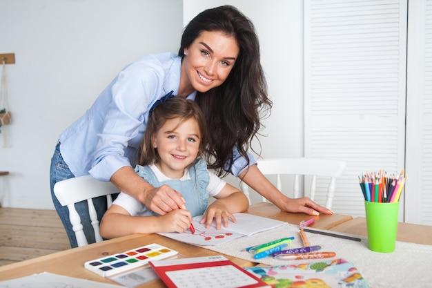 Улыбающиеся мама и дочка готовятся к урокам и рисуют за столом карандашами и красками