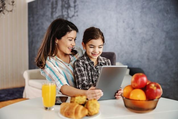 朝の食卓に座ってタブレットを使用して笑顔の母と娘。タブレットで漫画を見ている幸せな家族。