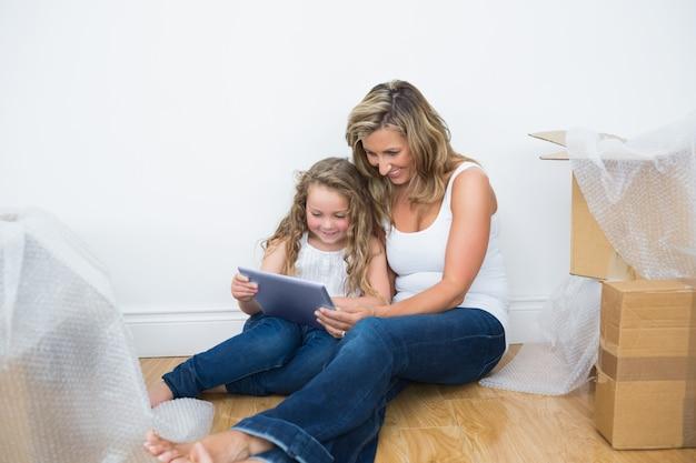 Улыбаясь мать и дочь с помощью планшетного компьютера