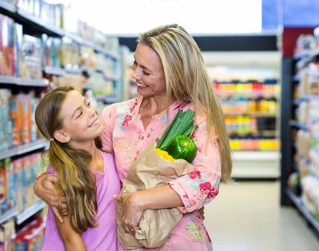 Улыбаясь мать и дочь с продуктовой сумкой