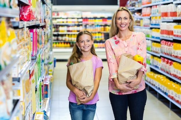 Улыбаясь мать и дочь с продуктовые сумки