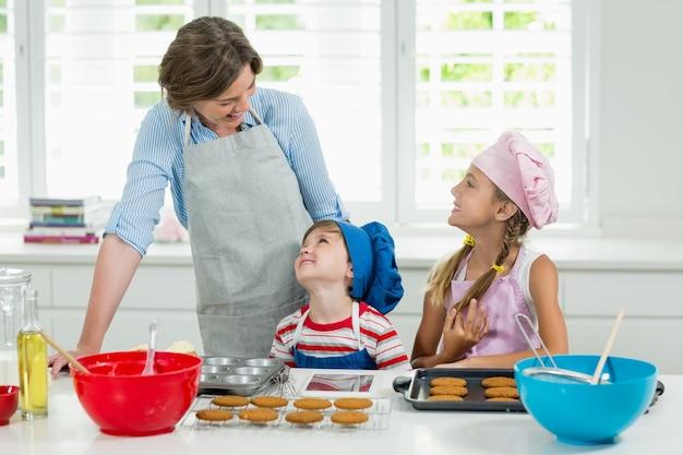 クッキーを準備している間、母親と子供がお互いにやり取りする笑顔