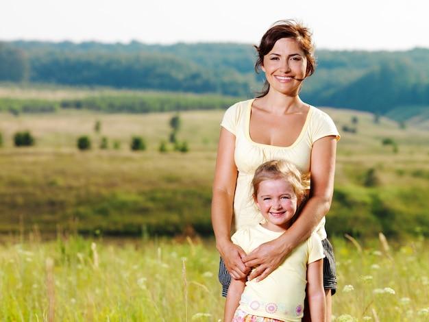 自然に笑顔の母と幼い娘。