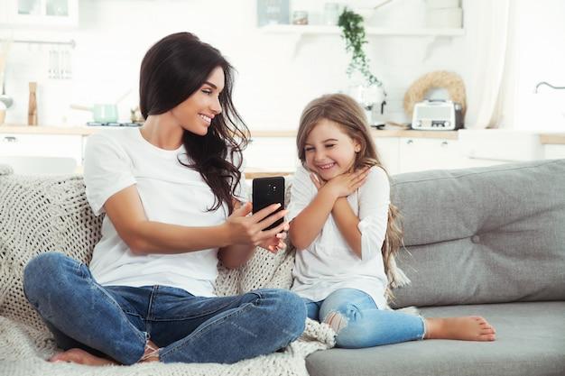 Улыбаясь, мать и маленькая дочь, играя в игры с смартфона