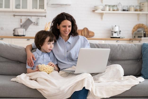 笑顔の母親と幼稚園の息子がノートパソコンで面白いビデオを見る