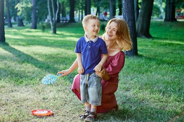 笑顔の母と幼い息子が一緒に屋外を歩く