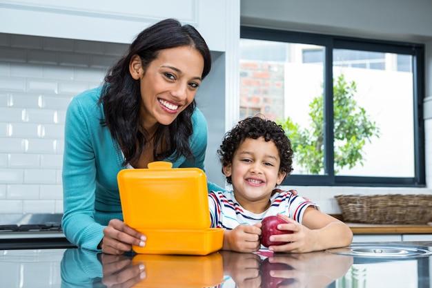 Улыбаясь мать и сын собирается съесть яблоко