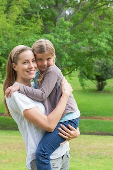 公園で娘を運んでいる笑顔の母