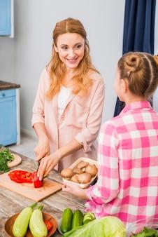 버섯 바구니를 들고 그녀의 딸을보고 칼로 피망을 절단 웃는 어머니