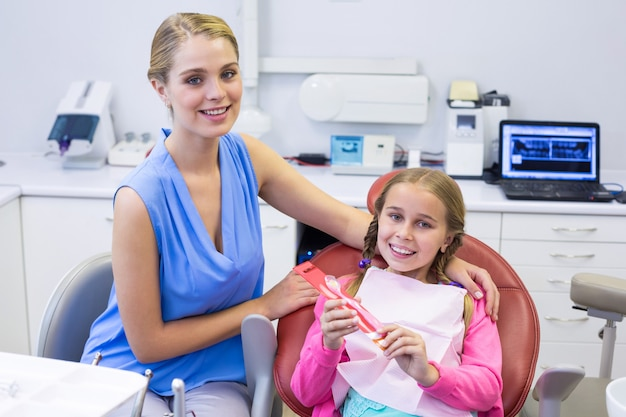 Smiling mother and daughter at dental clinic