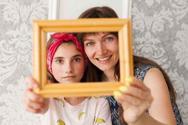 Smiling mother and daughter holding photo frame in front of their face
