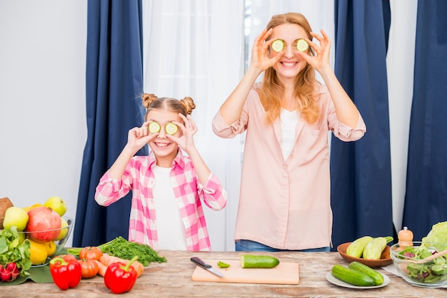 Smiling mother and daughter holding slice of cucumber in front of their eyes