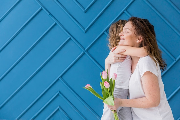 Smiling mother and daughter hugging each other holding tulip flowers against blue backdrop