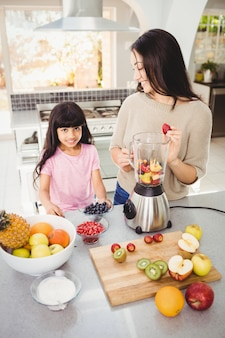 Smiling mother and daughter preparing fruit juice