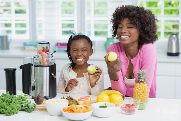 Smiling mother and daughter preparing strawberry smoothie in kitchen at home