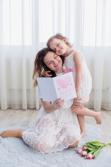 Smiling mother and daughter reading mother's day card together at home