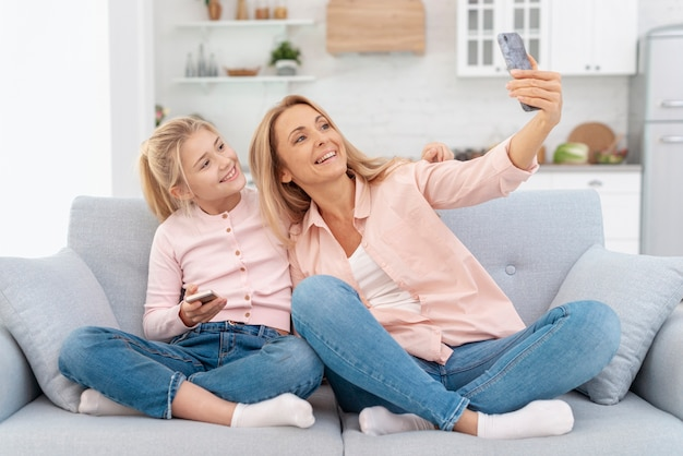 Smiling mother and daughter taking selfies