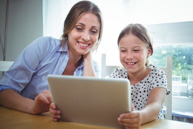 Smiling mother and daughter using digital tablet