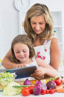 Smiling mother and daughter using tablet above table with vegetables