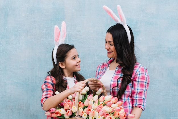 Smiling mother and daughter wearing bunny ears holding tulips basket looking at each other against blue wall