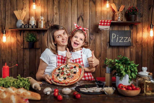 Smiling mother and daughter with cooked pizza and thumbs up