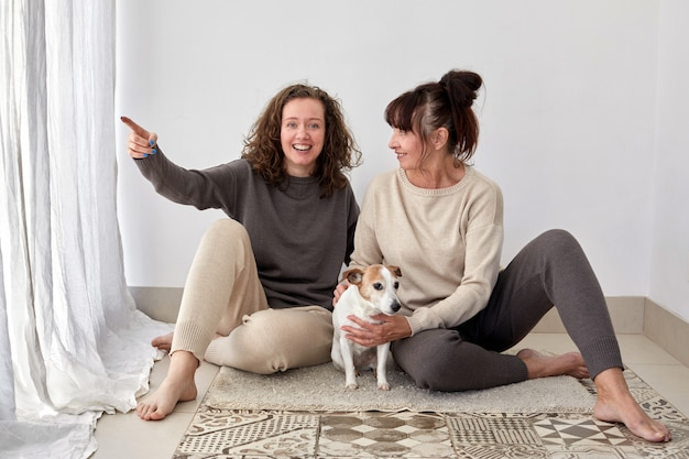 Smiling mother and daughter with dog at home