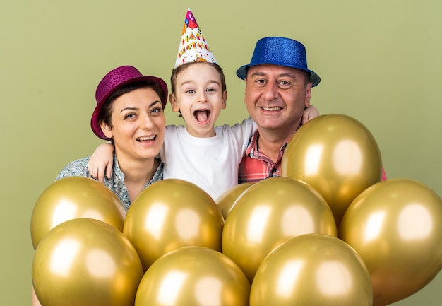 Smiling mother and father wearing party hats standing with their son and holding helium balloons isolated on olive green wall with copy space