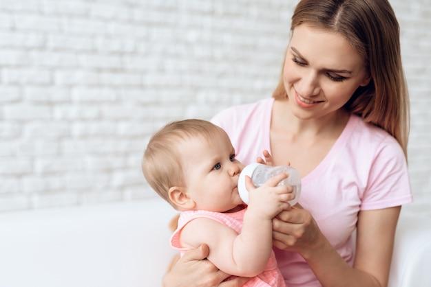 Smiling mother feeding baby milk bottle home.