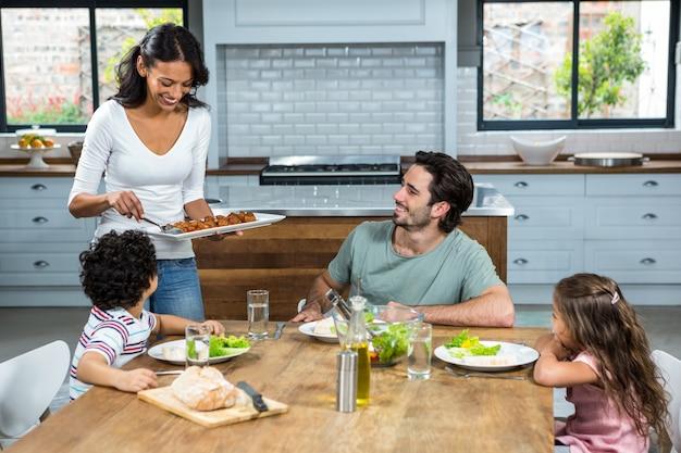 Улыбающаяся мать дает еду своим детям и мужу